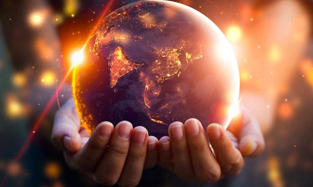 burned globe hands golden particles flares